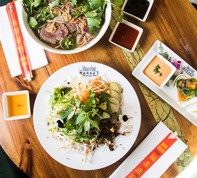 Scene of a table with a bowl of pho, summer salad and bun.