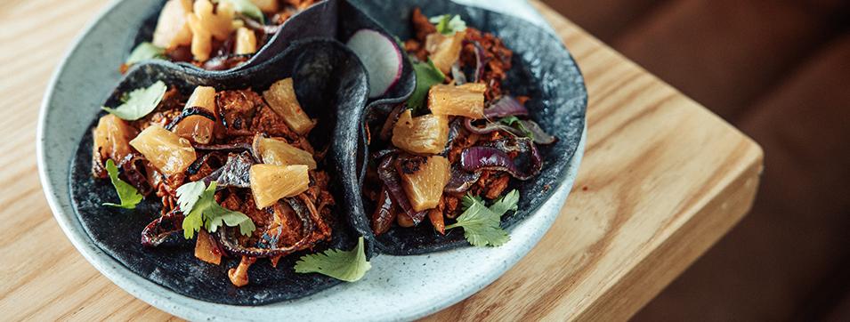 Tacos Al Pastor avec Pleurotes marines à l'achiote et aux piments mexicains, ananas, coriandre, oignon rouges, sauce aioli aux piments ancho.