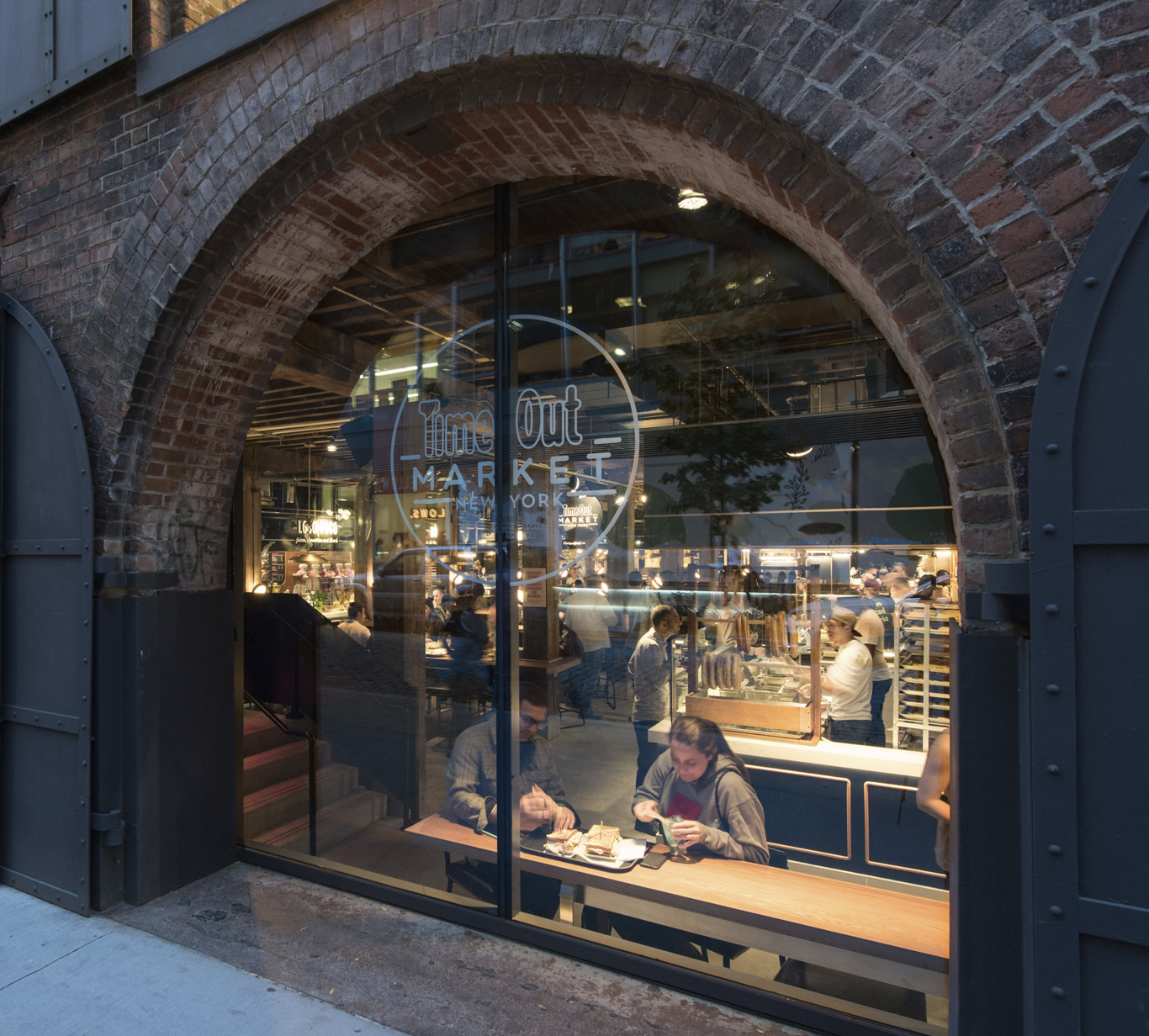 Window of Time Out Market New York framed by exterior brick