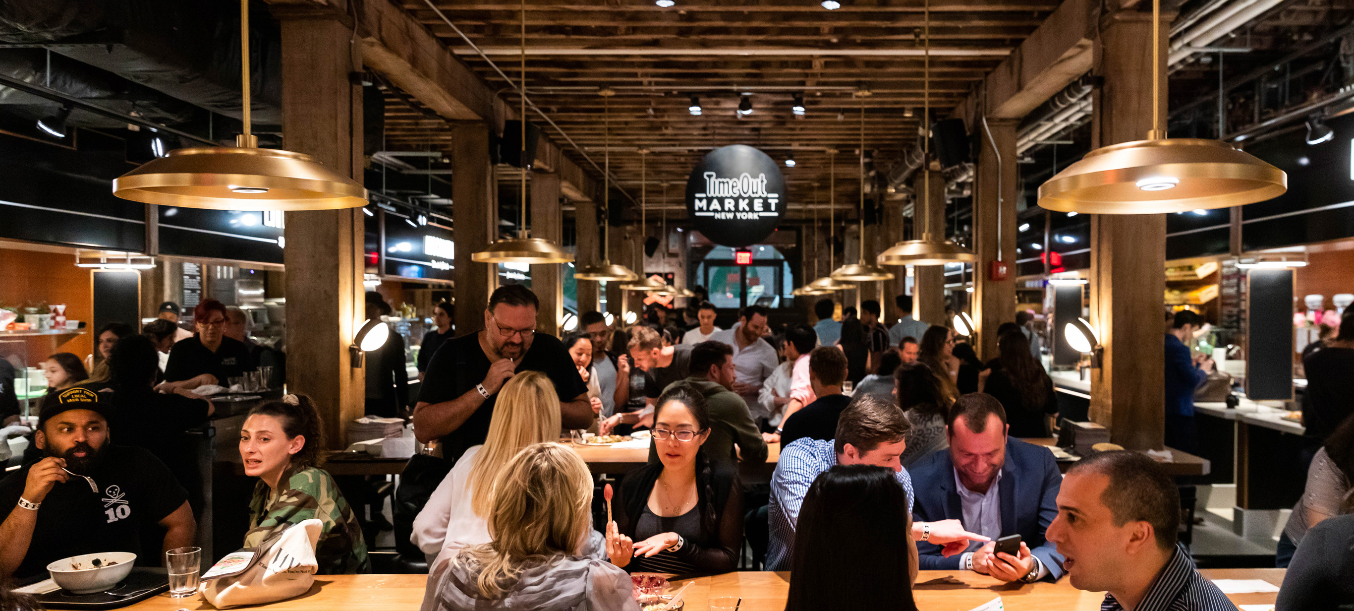 Busy scene of Time Out Market New York with diners at communal tables
